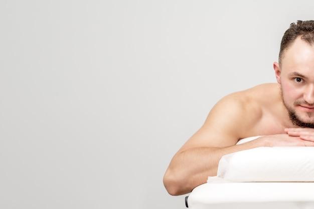 Jovem homem caucasiano deitado de frente na mesa de spa, esperando tratamento de beleza