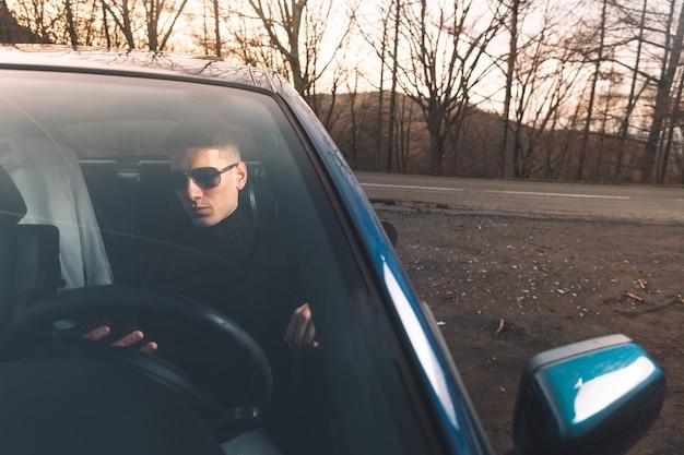 Jovem homem caucasiano dentro de um carro usando um smartphone