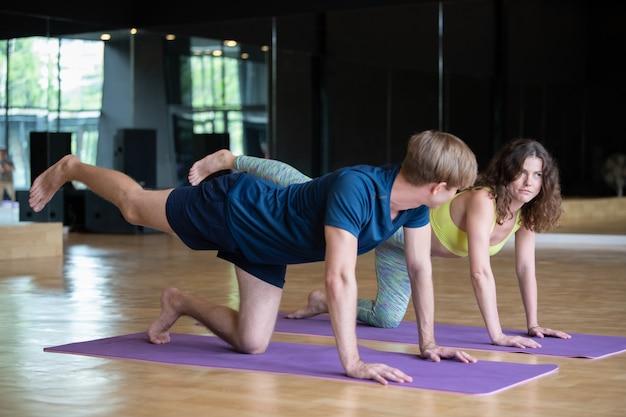Jovem homem caucasiano e mulher no treinamento de fitness de sala de aula de ioga