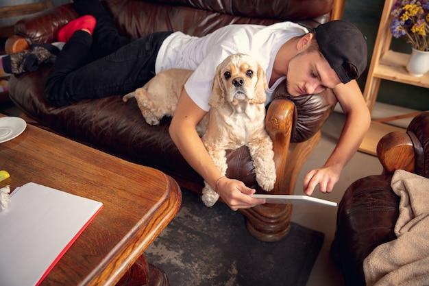 Jovem homem caucasiano e seu animal de estimação cocker spaniel americano de cor creme descansam em casa, vista de cima
