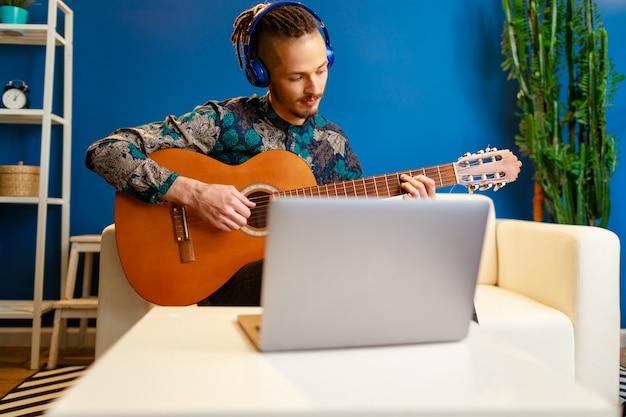 Jovem homem caucasiano elegante tendo aula de guitarra on-line em casa usando seu laptop