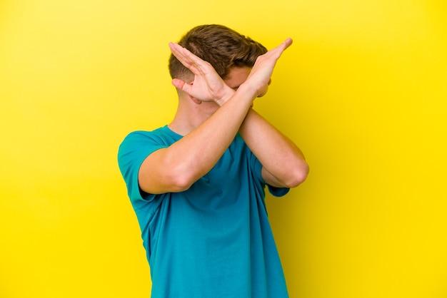 Jovem homem caucasiano em amarelo, mantendo os dois braços cruzados, o conceito de negação.