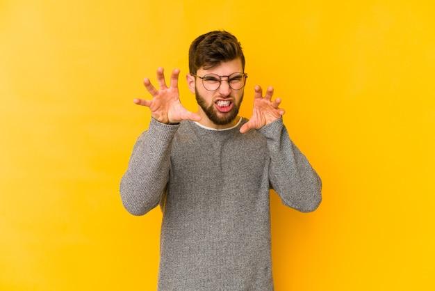 Jovem homem caucasiano em amarelo mostrando garras imitando um gato, gesto agressivo.