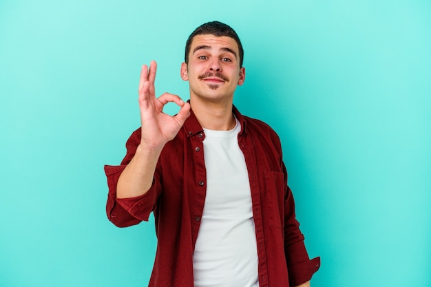 Jovem homem caucasiano em azul pisca um olho e segura um gesto de ok com a mão.