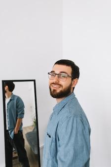 Jovem homem caucasiano em copos de pé para o espelho na sala de estar.