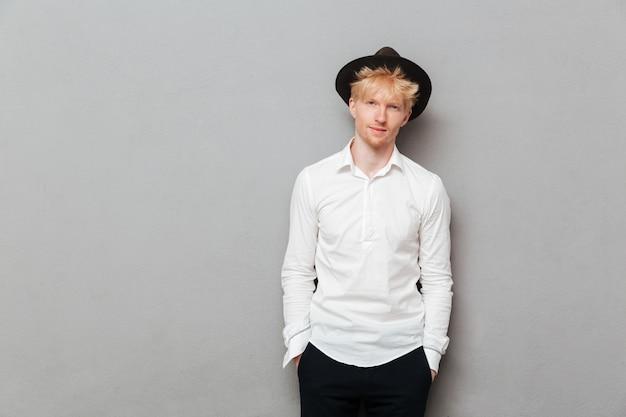 Jovem homem caucasiano em pé isolado sobre parede cinza