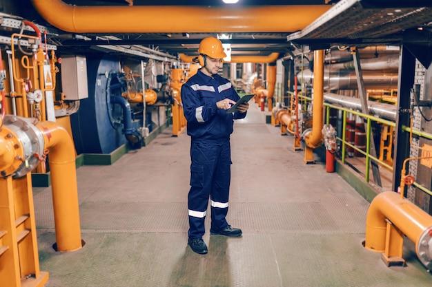 Jovem homem caucasiano em traje de proteção usando o tablet em pé na usina de aquecimento.