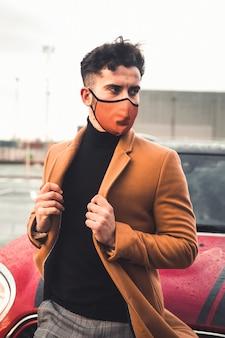 Jovem homem caucasiano em um estacionamento com um carro vermelho atrás