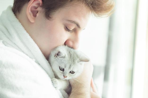 Jovem homem caucasiano em um roupão de banho está segurando um gatinho branco. ele fica perto da janela no início da manhã.