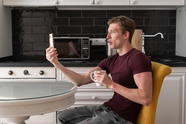 Jovem homem caucasiano em uma camiseta e jeans está sentado na cozinha com um smartphone na mão e falando em uma videochamada.