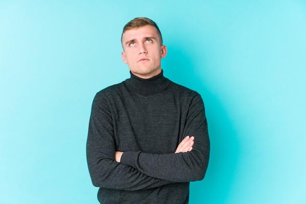 Jovem homem caucasiano em uma parede azul cansado