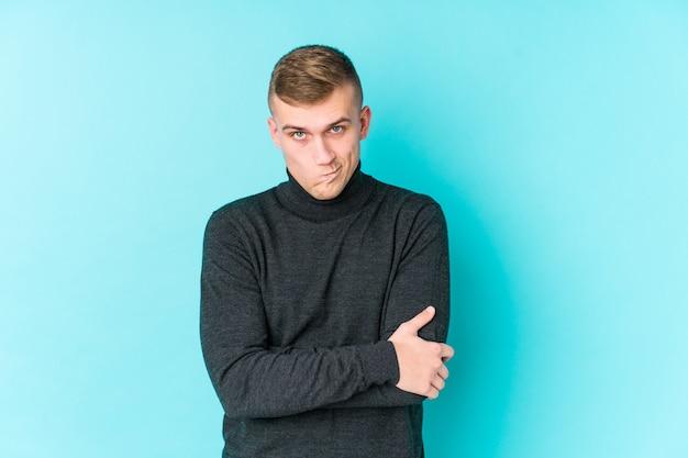 Jovem homem caucasiano em uma parede azul, cara carrancuda em desgosto, mantém os braços cruzados.