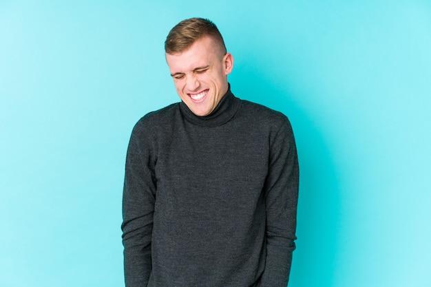 Jovem homem caucasiano em uma parede azul ri e fecha os olhos, sente-se relaxado e feliz.