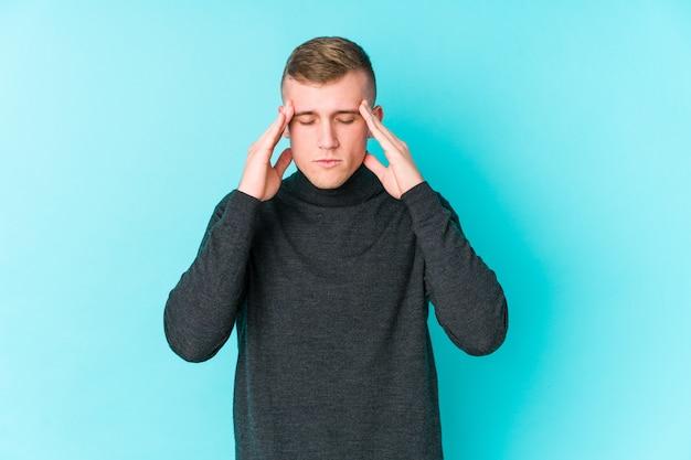 Jovem homem caucasiano em uma parede azul, tocando as têmporas e tendo dor de cabeça.