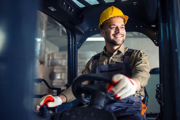 Jovem homem caucasiano em uniforme de trabalho e capacete amarelo operando empilhadeira na sala de armazenamento do armazém.