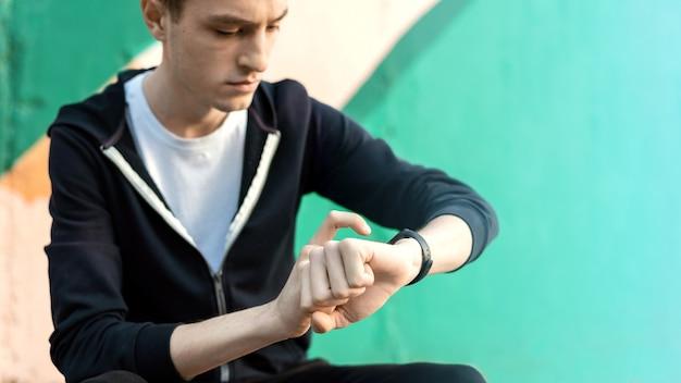 Jovem homem caucasiano está em sua pulseira de fitness em fundo multicolorido