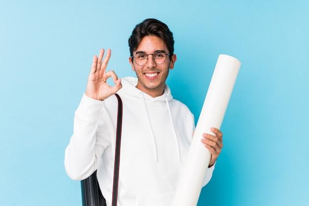 Jovem homem caucasiano estudando arquitetura alegre e confiante mostrando o gesto ok.
