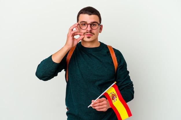 Jovem homem caucasiano estudando inglês em branco com os dedos nos lábios, mantendo um segredo.