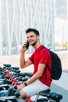 Jovem homem caucasiano falando ao telefone sentado em uma bicicleta alugada