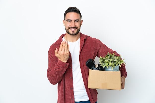 Jovem homem caucasiano fazendo um movimento ao pegar uma caixa cheia de coisas isoladas no fundo branco, convidando para vir com a mão. feliz que você veio