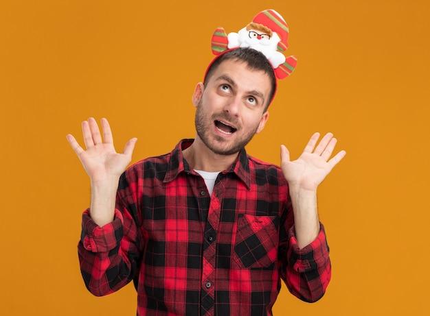 Jovem homem caucasiano impressionado com bandana de papai noel, mostrando as mãos vazias, olhando para cima, isolado na parede laranja