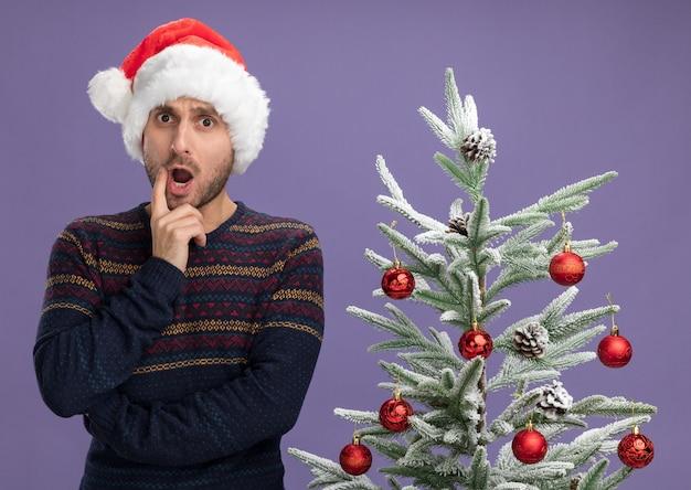 Jovem homem caucasiano impressionado com chapéu de natal em pé perto de uma árvore de natal decorada, olhando para a câmera, mantendo a mão no queixo isolado no fundo roxo