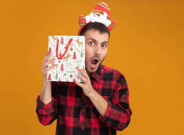 Jovem homem caucasiano impressionado com uma faixa de papai noel, segurando uma sacola de presente de natal perto da cabeça, olhando para a câmera isolada em fundo laranja