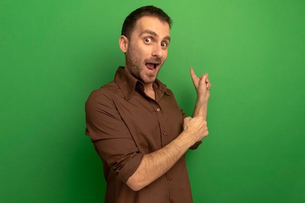 Jovem homem caucasiano impressionado olhando para a câmera apontando para trás, isolado em um fundo verde com espaço de cópia