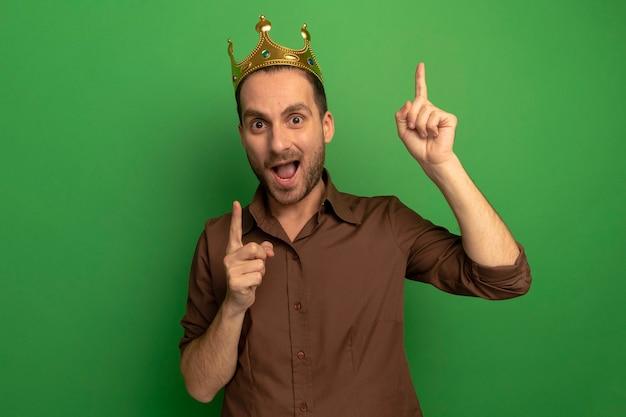 Jovem homem caucasiano impressionado usando coroa, olhando para a câmera apontando para cima, isolado em um fundo verde com espaço de cópia