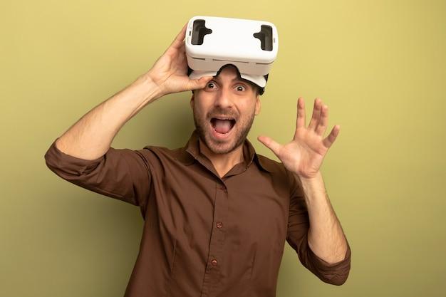 Jovem homem caucasiano impressionado usando fone de ouvido vr na testa, segurando-o olhando para a câmera, mostrando a mão vazia isolada em um fundo verde oliva com espaço de cópia