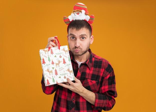 Jovem homem caucasiano impressionado usando uma faixa de papai noel segurando uma sacola de presente de natal, olhando para a câmera isolada em fundo laranja