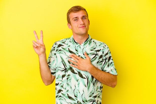 Jovem homem caucasiano isolado em amarelo, fazendo um juramento, colocando a mão no peito.