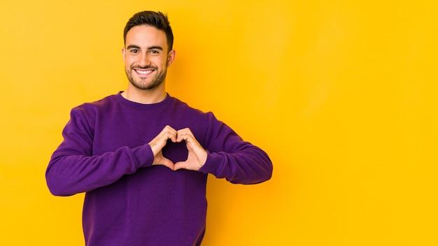 Jovem homem caucasiano isolado em amarelo sorrindo e mostrando uma forma de coração com as mãos.