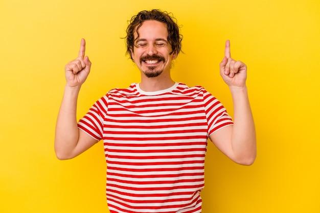 Jovem homem caucasiano isolado em fundo amarelo indica com os dois dedos anteriores mostrando um espaço em branco.