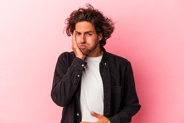 Jovem homem caucasiano isolado em rosa bakcground sopra nas bochechas, tem expressão cansada. conceito de expressão facial.