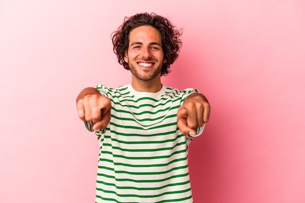 Jovem homem caucasiano isolado em sorrisos alegres rosa bakcground apontando para frente.