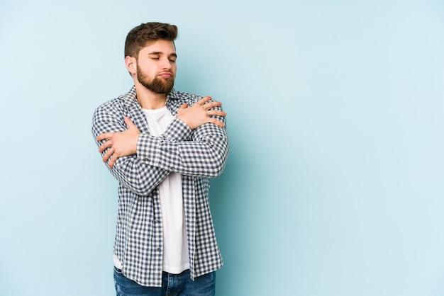 Jovem homem caucasiano isolado em um abraço azul, sorrindo despreocupado e feliz.
