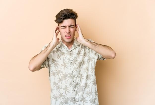 Jovem homem caucasiano isolado em um espaço bege, cobrindo as orelhas com os dedos, estressado e desesperado por um ambiente barulhento.