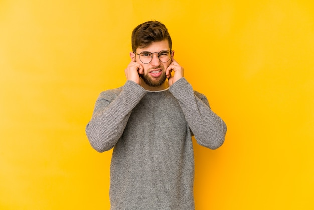Jovem homem caucasiano isolado em um fundo amarelo, cobrindo as orelhas com os dedos, estressado e desesperado por um ambiente barulhento.