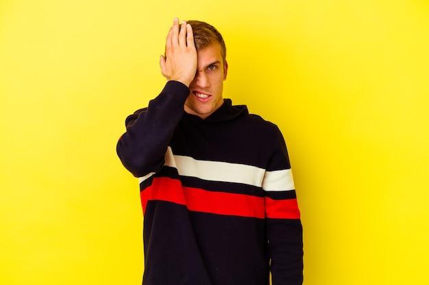 Jovem homem caucasiano isolado em um fundo amarelo, esquecendo de algo, batendo na testa com a palma da mão e fechando os olhos.