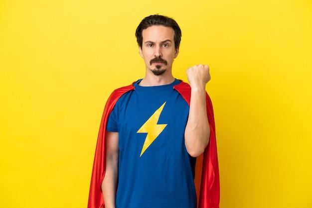 Jovem homem caucasiano isolado em um fundo amarelo fantasiado de super-herói.