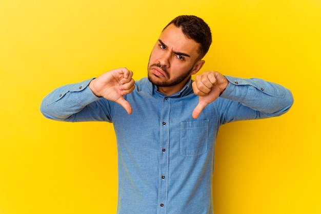 Jovem homem caucasiano isolado em um fundo amarelo, mostrando o polegar para baixo, o conceito de decepção.