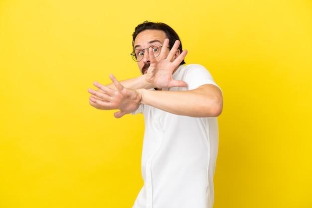 Jovem homem caucasiano isolado em um fundo amarelo, nervoso, esticando as mãos para a frente
