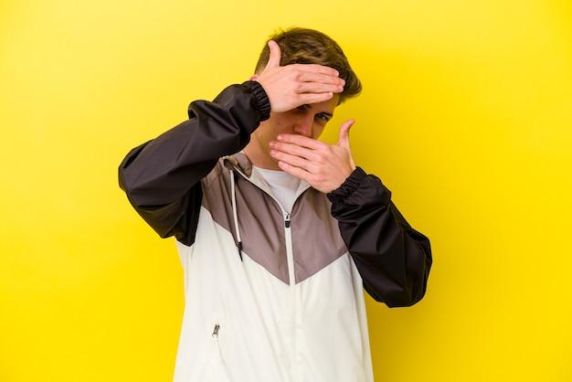 Jovem homem caucasiano isolado em um fundo amarelo pisca para a câmera por entre os dedos, o rosto coberto de vergonha.