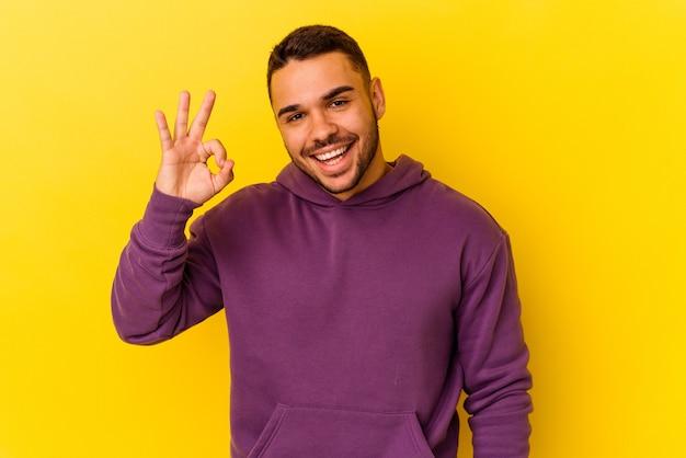 Jovem homem caucasiano isolado em um fundo amarelo pisca um olho e segura um gesto de ok com a mão.