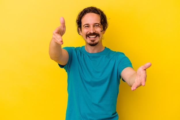 Jovem homem caucasiano isolado em um fundo amarelo se sente confiante em dar um abraço para a câmera.