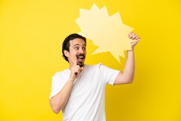Jovem homem caucasiano isolado em um fundo amarelo segurando um balão de fala vazio e pensando