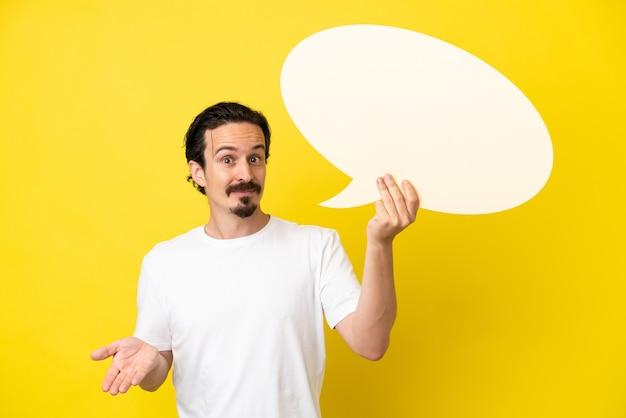 Jovem homem caucasiano isolado em um fundo amarelo segurando um balão de fala vazio e tendo dúvidas