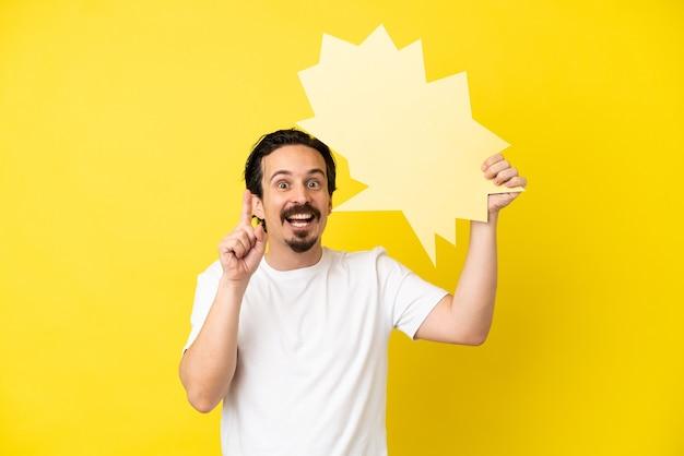Jovem homem caucasiano isolado em um fundo amarelo segurando um balão vazio com expressão de surpresa
