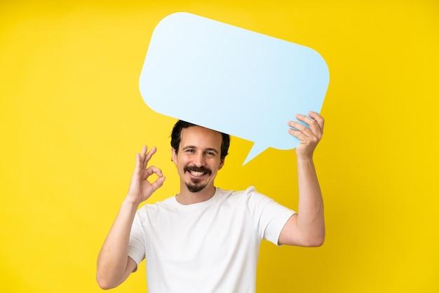 Jovem homem caucasiano isolado em um fundo amarelo segurando um balão vazio e fazendo sinal de ok